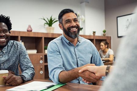 Zwei Geschäftsleute, die sich beim Sitzen im Konferenzraum die Hände schütteln. Geschäftsmann aus dem Nahen Osten schütteln der Geschäftsfrau die Hand. Porträt des glücklichen lächelnden lateinischen Mannes, der Abkommen mit einem Händedruck abschließt. Standard-Bild