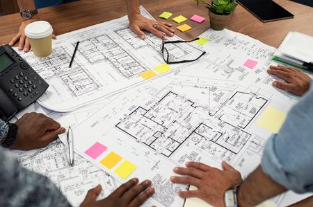 Primer plano de manos multiétnicas en planos en la oficina de arquitectos. Equipo de diseñadores e ingenieros trabajando juntos en el nuevo complejo residencial. Vista superior del diseño de planos de casas y edificios en mesa de madera. Foto de archivo