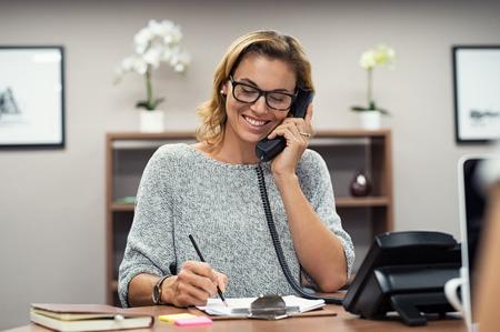 Piękna dojrzała kobieta rozmawia przez telefon w kreatywnym biurze. Szczęśliwy uśmiechający się businesswoman odbierania telefonu przy biurku. Dorywczo biznes kobieta siedzi przy biurku, co telefon i robienie notatek na notebooku.