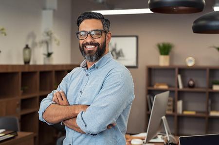 Portrait d'un homme d'affaires heureux et mature portant des lunettes et regardant la caméra. Homme satisfait multiethnique avec barbe et lunettes se sentant confiant au bureau. Homme d'affaires prospère du Moyen-Orient souriant dans un bureau créatif. Banque d'images