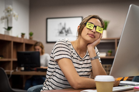Sleeping businesswoman covering her eyes with sticky notes on eyeglasses. Young casual woman rest with eyes drawn on adhesive notes at creative office. Girl leaning face on hand covering specs with open eye sticky notes. Standard-Bild