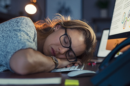 Mature business woman wearing eyeglasses and sleeping on computer keyboard in office. Closeup face of tired businesswoman doing overtime sleeping. Portrait of blonde sleepy woman in dark office. Overwork and procrastination concept.