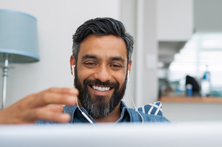 Portrait of happy mature man making hand gestures while conversing with a video call at laptop with earphones. Cheerful casual businessman doing video calling at home. Middle eastern man relaxing at home while using digital tablet.