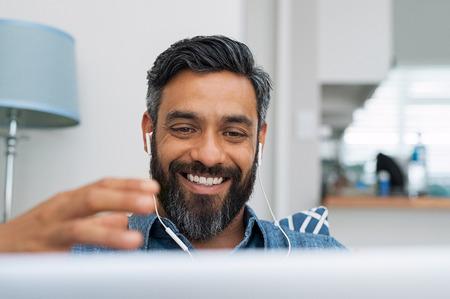 Retrato de hombre maduro feliz haciendo gestos con las manos mientras conversa con una videollamada en la computadora portátil con auriculares. Alegre empresario casual haciendo videollamadas en casa. Hombre de Oriente Medio relajante en casa mientras usa tableta digital. Foto de archivo