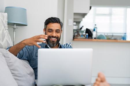 Hombre maduro feliz relajándose en el sofá mientras se realizan videollamadas usando la computadora portátil en casa. Hombre latino sentado en el sofá y haciendo una videollamada. Sonriente hombre de negocios del Medio Oriente haciendo video chat en línea mientras gesticula con las manos. Foto de archivo