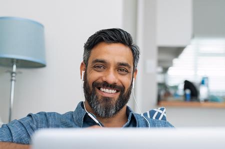 Retrato de hombre feliz usando laptop con auriculares mientras está acostado en el sofá. Hombre casual en videollamada acostado en el sofá mientras escucha música con la computadora. Hombre maduro del Medio Oriente con auriculares mirando a la cámara con una gran sonrisa.