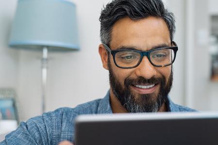 Hombre maduro relajado en casa con tableta digital. Hombre hispano hermoso que usa la computadora portátil en el sofá. Chico multiétnico confiado con gafas y barba usando laptop digital.