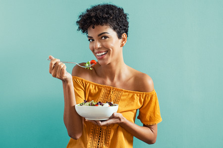 Beautiful young african woman eating fresh salad with cherry tomatoes. Portrait of happy smiling woman in diet isolated on blue background. Cheerful brazilian girl with curly hair eating fresh vegetable while looking at camera with copy space. Stock Photo