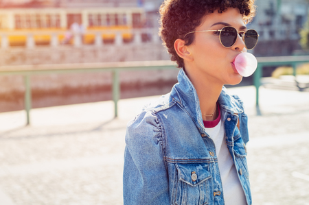Young beautiful african woman in sunglasses with curly hair puffs bubble of chewing gum in summer. Brazilian young woman inflates pink chewing gum. Stylish woman making bubblegum of chewing gum.