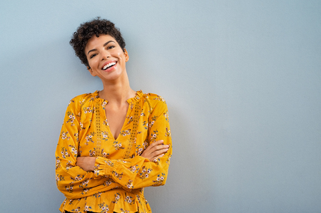 Portrait of beautiful cheerful girl smiling and looking at camera. Happy african woman in casual standing on blue background. Brazilian stylish woman with crossed arms and curly hair isolated with cop