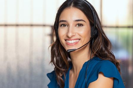 Klantenondersteuningsvrouw die lacht en naar de camera kijkt. Portret van een gelukkige telefoniste voor klantenondersteuning bij het callcenter met een headset. Vrolijke executive tot uw dienst werken op kantoor.
