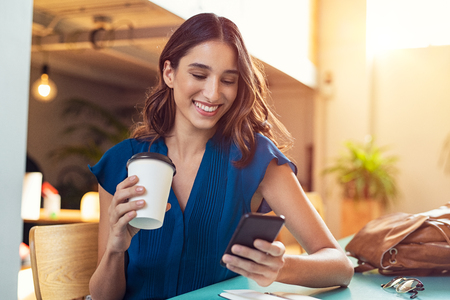 Young beautiful woman holding coffee paper cup and looking at smartphone while sitting at cafeteria. Happy university student using mobile phone. Businesswoman in casual clothes drinking coffee, smili 스톡 콘텐츠