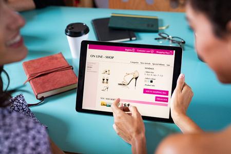Primer plano de una mujer haciendo compras en línea en tableta digital en la cafetería. Mujer compra zapatos elegantes en el sitio web del mercado en línea. Vista posterior de dos niñas con tableta digital para comprar en línea.