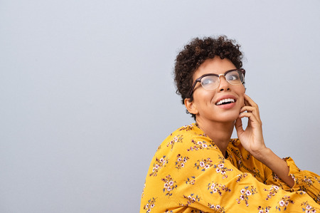 Happy thinking young woman looking away with fashion eyeglasses. African american female student thinking about future while isolated against grey wall. Brazilian with spectacles looking away and smiling.