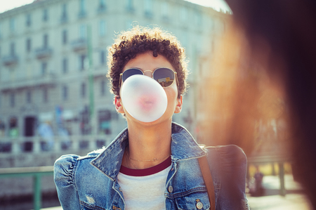 Young african girl in sunglasses with curly hair puffs bubble of chewing gum in city street. Brazilian young woman inflates pink chewing gum. Stylish woman making bubblegum of chewing gum. Banco de Imagens