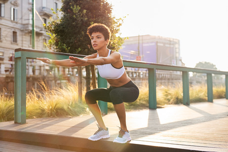 Sporty woman doing squats exercises in the city. Brazilian girl doing sit ups on stairs. Concentrated woman doing warmup squat in urban background. Stock Photo
