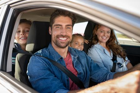 Souriante jeune famille avec deux enfants assis dans la voiture et au volant. Détente en famille pendant le voyage en regardant la caméra. Portrait d'un père heureux dans une voiture avec sa femme, son fils et sa fille.
