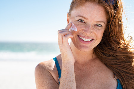 Lächelnde junge Frau, die Sonnencreme auf Gesicht am Strand aufträgt, mit Kopienraum. Schöne reife Frau mit roten Haaren, die den Sommer auf See genießen. Porträt eines glücklichen Mädchens mit Sonnencreme auf ihrer zarten Haut mit Sommersprossen und Blick in die Kamera. Standard-Bild