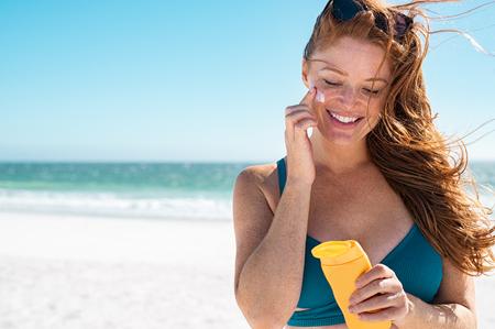 Hermosa mujer joven en bikini azul en la playa aplicando protector solar en la cara para protegerse en un día soleado. Mujer madura con pecas y cabello rojo disfrutando de las vacaciones de verano mientras se aplica loción bronceadora. Retrato de dama sonriente con piel sana.