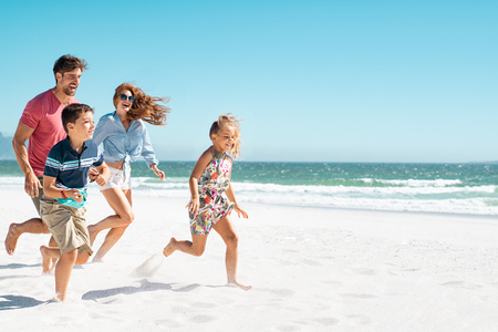 Cheerful young family running on the beach with copy space. Happy mother and smiling father with two children, son and daughter, having fun during summer holiday. Playful casual family enjoying playing at beach during vacaton.