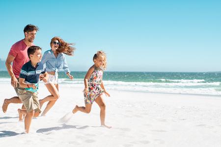 Wesoła młoda rodzina działa na plaży z miejsca na kopię. Szczęśliwa matka i uśmiechnięty ojciec z dwójką dzieci, synem i córką, bawią się podczas letnich wakacji. Zabawna, swobodna rodzina, która bawi się na plaży podczas wakacji.