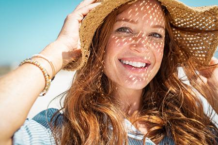 Porträt einer schönen Frau mit Strohhut mit großer Krempe am Strand und Blick in die Kamera. Nahaufnahmegesicht des attraktiven lächelnden Mädchens mit Sommersprossen und rotem Haar. Glückliche reife Frau, die Sommerferien auf See genießt.