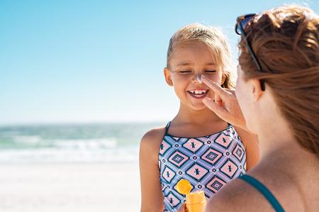 Madre joven que aplica protector solar protector en la nariz de la hija en la playa. Mano de mujer poniendo crema solar en la cara del niño. Niña linda con bloqueador solar en la playa con espacio de copia.