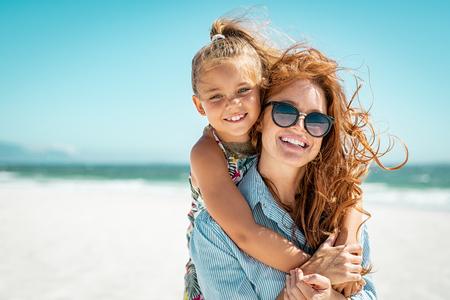 Lächelnde Mutter und schöne Tochter, die Spaß am Strand haben. Porträt einer glücklichen Frau, die einem süßen kleinen Mädchen mit Kopienraum eine Huckepackfahrt gibt. Porträt eines glücklichen blonden Kindes, das ihre Mutter während der Sommerferien mit Brille am Strand umarmt. Standard-Bild