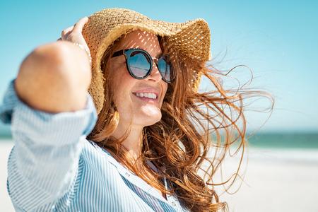 Vista laterale di occhiali da sole d'uso della bella donna matura che godono alla spiaggia. Giovane donna sorridente in vacanza che guarda lontano mentre si gode la brezza marina che indossa un cappello di paglia. Ritratto del primo piano della ragazza attraente che si rilassa in mare.