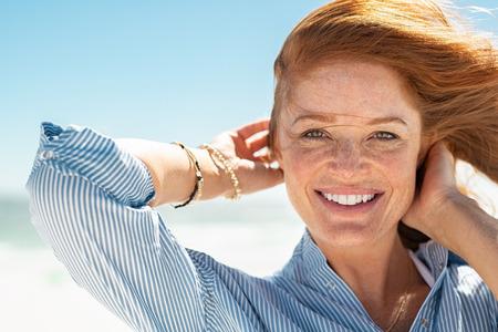 Portrait der schönen reifen Frau mit dem Wind flatternden Haaren. Nahaufnahmegesicht der gesunden jungen Frau mit den Sommersprossen, die am Strand sich entspannen. Fröhliche Dame mit roten Haaren und blauer Bluse, die am Meer steht und eine Brise genießt, die in die Kamera schaut.