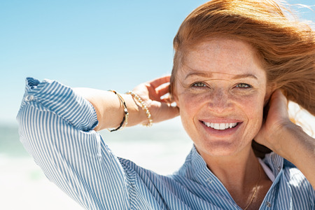 Portrait of beautiful mature woman with wind fluttering hair. Closeup face of healthy young woman with freckles relaxing at beach. Cheerful lady with red hair and blue blouse standing at seaside enjoying breeze looking at camera. Фото со стока