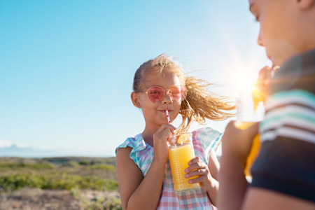 Portrait of little girl drinking orange juice in a glass with straw. Rear view of brother drinking with sister at outdoor park. Boy and cute girl with sunglasses suck from the straw a fresh pineapple juice outdoor with copy space. 版權商用圖片