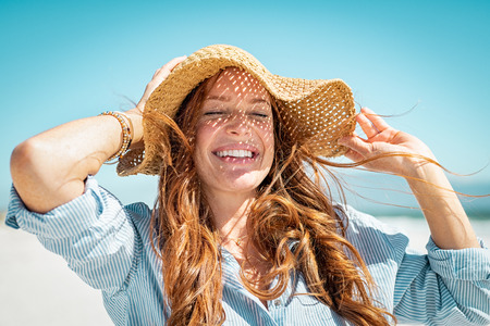 Closeup face of mature woman wearing straw hat enjoying the sun at beach. Happy young woman smiling during summer vacation at sea. Portrait of beautiful lady relaxing at beach while holding large brim for the wind. Stock Photo