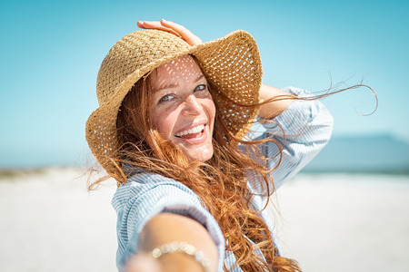 Portret van mooie volwassen vrouw in casual dragen van stro hoed in zonnige warme dag aan zee. Vrolijke jonge vrouw die lacht op het strand tijdens de zomervakantie. Gelukkig meisje met rood haar en sproeten die van de zon genieten. Stockfoto