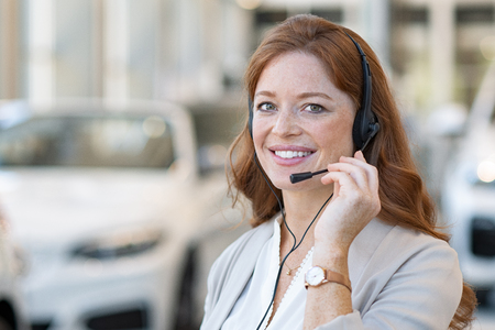 Beautiful female customer support wearing headset and looking at camera. Portrait of smiling woman customer service representative working with cars in background. Young call center operator at car rental office. Stock fotó