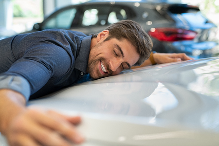 Happy young man hugging his new car in showroom. Satisfied guy with closed eyes embracing the hood of the automobile. Dreaming man lying on car bonnet hugging it. Фото со стока