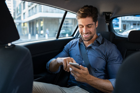 Happy smiling businessman man typing message on phone while sitting in a taxi. Young businessman in formal clothing using smartphone while sitting on back seat in car. Cheerful guy messaging wirth cellphone.