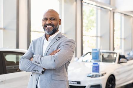 Glimlachende zakenman permanent met gekruiste armen in nieuwe auto showroom. Zelfverzekerde senior autodealer die bij de dealer staat terwijl hij naar de camera kijkt. Portret van professionele zwarte verkoper in luxe autoshowroom. Stockfoto