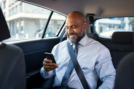 Successful african businessman working on phone smiling witting in car. Portrait of mature smiling business man in formal clothes using smartphone while sitting on back seat of luxury business car. Senior formal man reading confirmation mail on smartphone and smiling in a taxi. Imagens