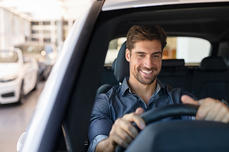 Young smiling man examining a new car in a showroom. Happy guy feeling comfortable sitting on driver seat in his new car at showroom. Man ready to make first test drive. 스톡 콘텐츠