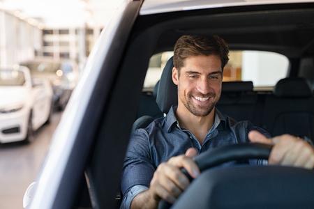Jeune homme souriant examinant une nouvelle voiture dans une salle d'exposition. Heureux gars se sentant à l'aise assis sur le siège du conducteur dans sa nouvelle voiture à la salle d'exposition. Homme prêt à faire le premier essai routier.