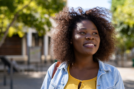 Portrait of curvy african woman thinking while looking away on the street. Closeup face of beautiful young african american woman smiling. Cheerful casual student girl with curly hair enjoying summer.