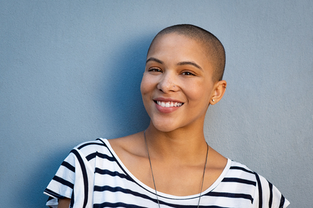 Closeup portrait of beautiful stylish woman on lightblue background. Smiling bald girl looking at camera isolated against blue background with copy space. Cheerful and satisfied young woman with shaved head in casual.
