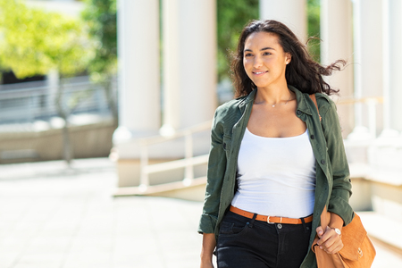 Young attractive woman walking in city street and looking away. Beautiful latin girl in casual with urban background. Hispanic casual woman smiling and walking on a bright sunny day with wind in the hair.
