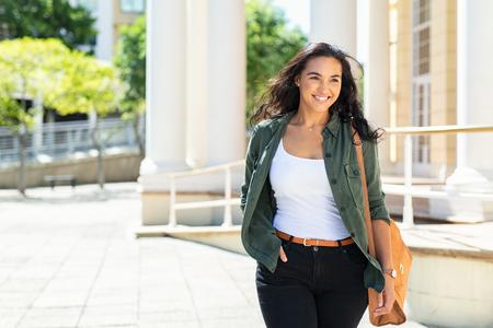 Femme naturelle assez décontractée marchant dans la rue urbaine et regardant loin. Joyeuse fille latine avec sac voyageant à travers la ville. Belle jeune femme souriante en plein air.