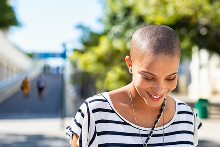 Portrait of happy and young bald woman smiling. Carefree trendy girl with bald head after cancer chemotherapy treatment. Stylish and beautiful woman feeling free in a city street.