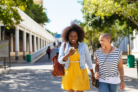 Young women friends using smartphone outdoor. Cheerful trendy girls in casual walking outdoor while reading message and laughing. Beautiful women using mobile phone while walking on city street.