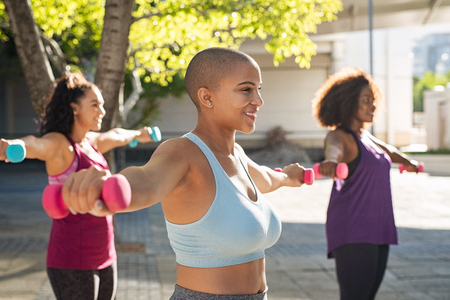 Group of curvy women in training session of aerobics using dumbbells at park. Side view of bald woman doing exercise with other people in background outdoor. Team of three oversize girls using fitness weights outdoor. Фото со стока