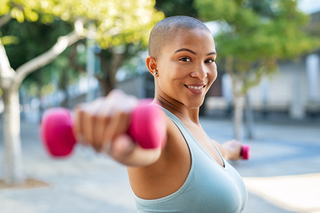 Portrait of happy bald woman exercising while looking at camera. Smiling girl doing sports outdoors with dumbbells lifting weights. Fit fitness girl in sportswear exercising outside to slim down. Stockfoto