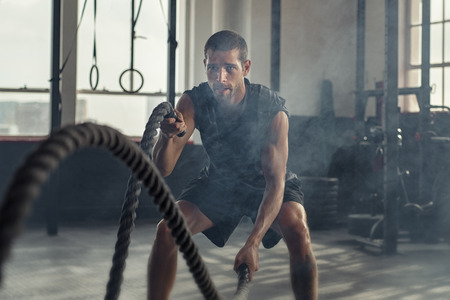 Strong young man working out with battle ropes in a crossfit gym. Muscular sportsman doing cross excursion with ropes in workout gym. Determined guy using battle rope while doing physical training. 免版税图像